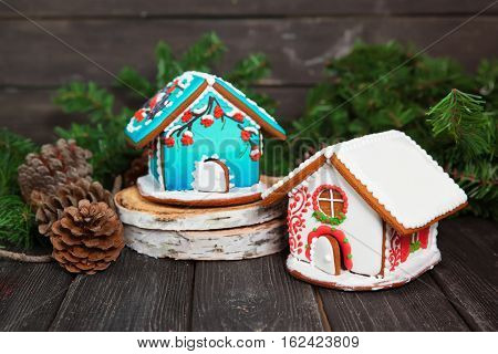 Two christmas gingerbread houses on wooden table, bullfinches and rowan decor.
