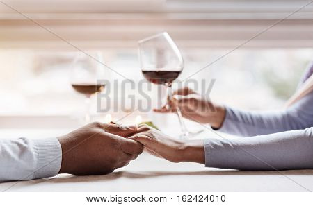 Romantic dinner for two. Young cheerful peaceful African American couple sitting in the restaurant and having the date while expressing love and holding wineglasses