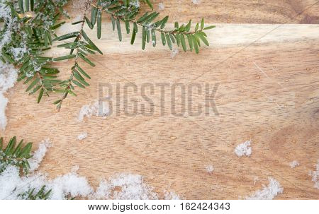 Wooden board with hemlock evergreen and snow along borders with room for text background