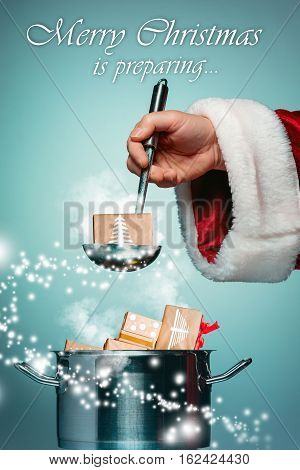 The Santa hand holding a ladle or kitchen spoon and ready for Christmas time on blue studio background. Collage and conceptual image