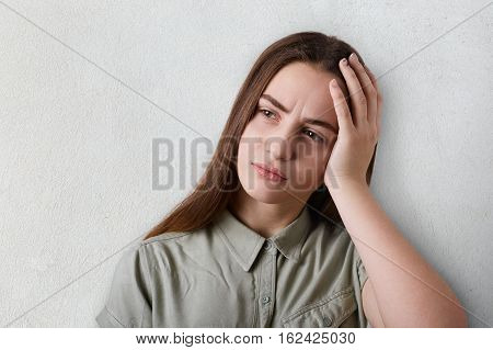 A portrait of thoughtful girl with long dark hair and big brown eyes wearing grey T-shirt having a sad expression holding her hand on her head. A tired girl having deep thoughts about something