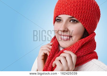 A photo of attractive young hazel-eyed woman with charming smile wearing warm winter clothes looking into distance holding a scarf with her hands standing on blue background. Winter seasonal concept
