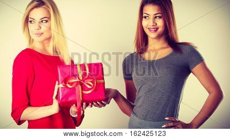 Occasions gifts people concept. Beautiful women blonde caucasian girl and mulatto with red gift box toned image