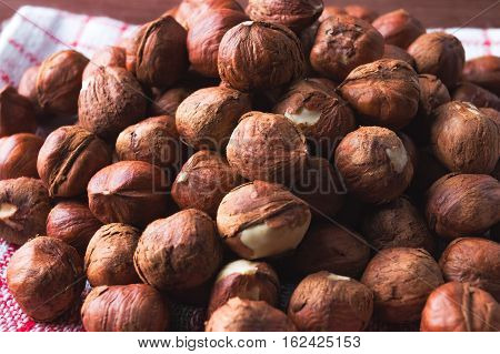 Hazelnuts pile on vintage kitchen dishcloth. Flat lay top view. Closeup. Vegan healthy food concept.