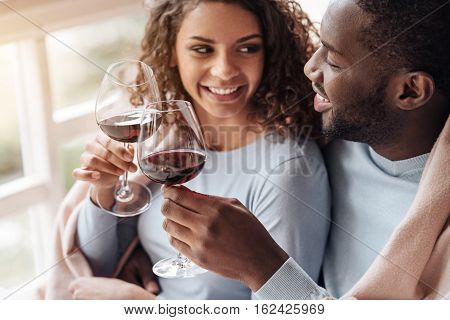 Dead gone on you. Delighted smiling cute African American couple sitting in the restaurant and looking at each other while being covered with the blanket and drinking wine
