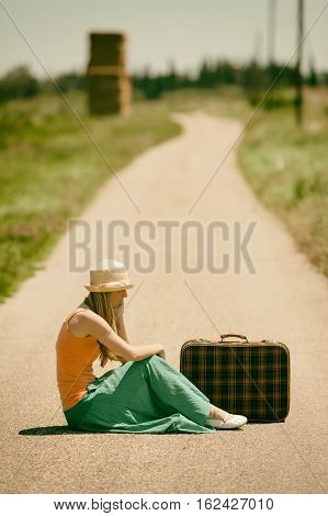 Lonely woman is sitting on country road with old suitcase. She is traveling alone. Intentionally toned.