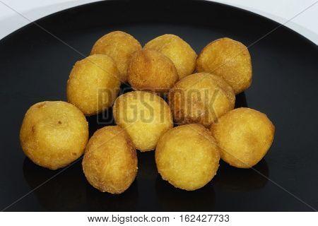 Thai snack fried potato balls on black plate.jpg