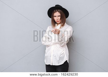 Portrait of angry upset woman pointing finger at camera isolated on a gray background