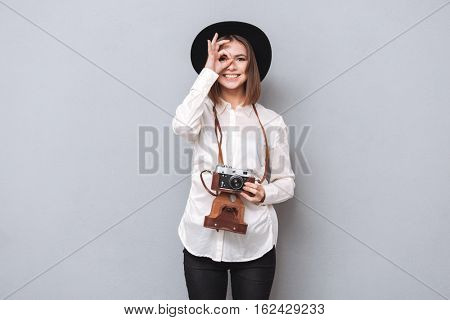 Portrait of a young smiling woman in hat holding retro camera and looking through a hole made with her fingers