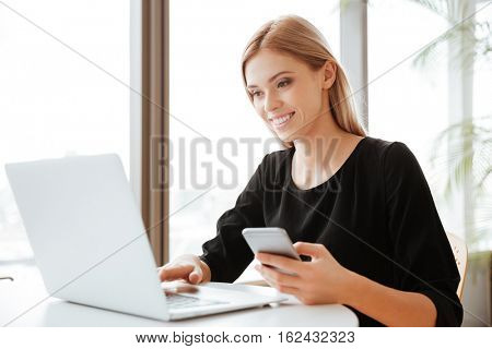 Picture of attractive young lady worker sitting in office while using laptop computer and chatting by telephone. Look at computer