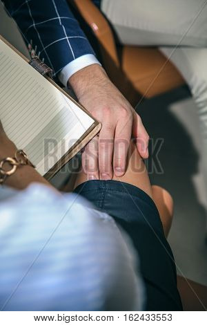 Closeup of boss putting hand over legs of blonde secretary in the office. Sexual harassment at work concept.