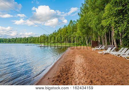 Beautiful deserted sandy beach forest lake with white deckchairs on forest and blue sky background