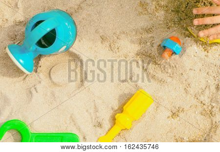 Children playing sandbox colorful toys top view