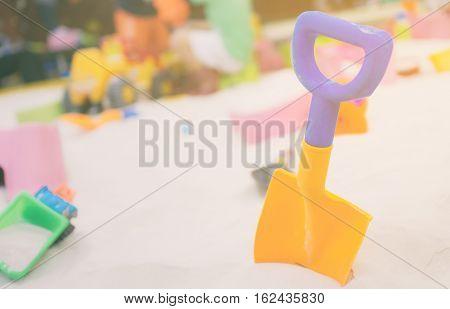 Colorful toy shovel in children sandbox playground.
