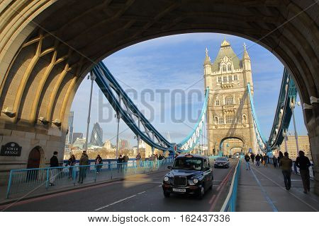 LONDON, UK - JANUARY 16, 2016: A black taxi on the Tower Bridge with the Gherkin in the background