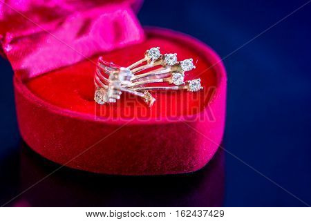 gold earrings stud in red box isolated.