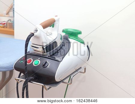 Modern electric iron on ironing board holder