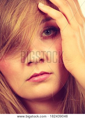 Sad Blonde Woman With Hand On Face