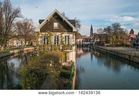 Strasbourg, water canal in Petite France area. Half timbered houses and trees in Grand Ile