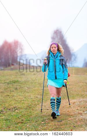 Young Blond Girl Practicing Nordic Walking In A Meadow