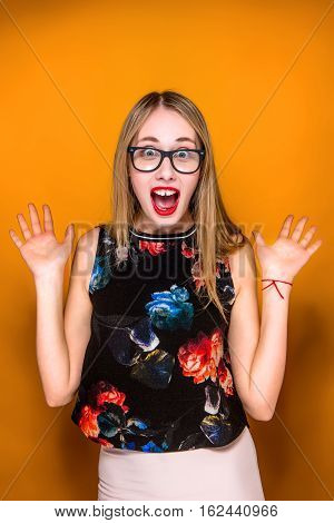 Portrait of young woman with glasses and shocked facial expression on orange studio background