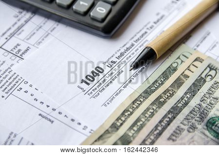 tax forms 1040 with the glasses money and the pen
