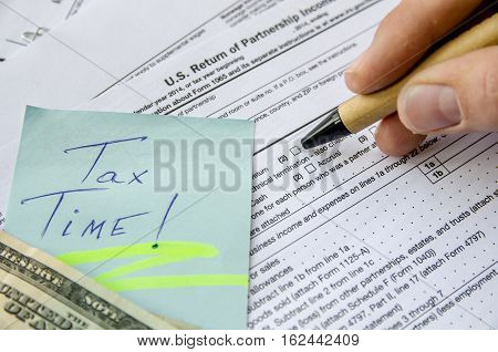 man filling Tax forms 1065 with dollar