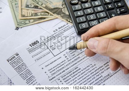 man filling Tax forms 1065 with calculator