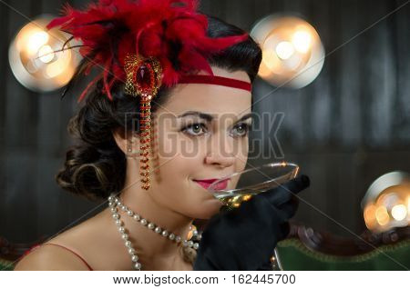 Retro portrait of smiling middle aged beautiful woman with glass of wine dressed in Great Gatsby style