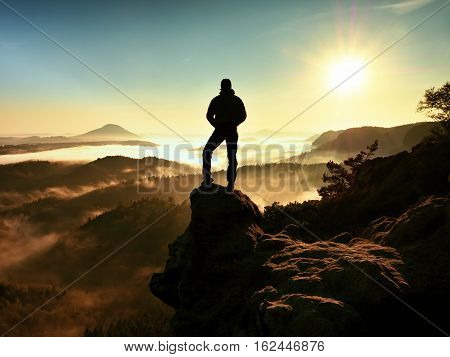 Man Standing High On Cliff. Hiker Climbed Up To Rocky Peak And Enjoy View
