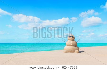 Positive sandy snowman in black eyeglasses and carrot nose at sunny tropical ocean beach. Happy New Year and Merry Christmas travel destinations for tropical vacations concept