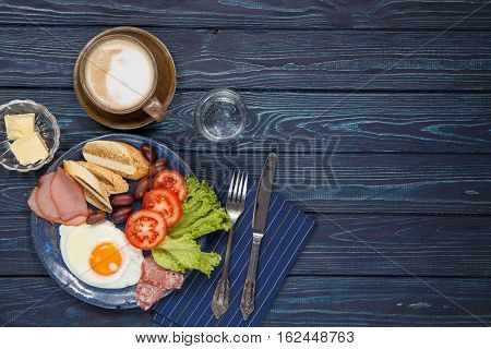 Substantial breakfast with fried egg salad bacon bread and coffee top view