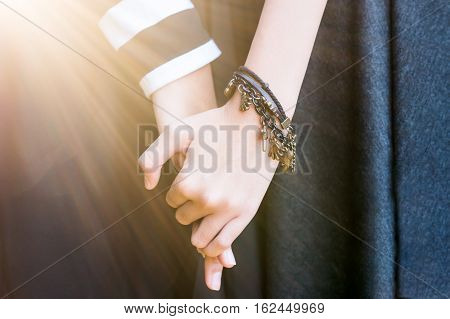 Yong teens Couple girls clasping hands with  flare.