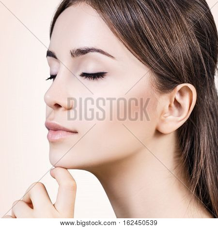Beautiful sensual woman face over beige background