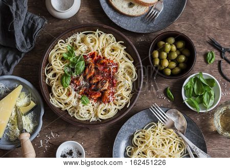 Mediterranean style lunch. Spaghetti with canned mussels and tomato sauce. On a wooden table top view. Flat lay