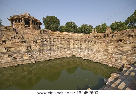 MODHERA, INDIA - NOVEMBER 1, 2007: Ancient stepped water tank in front of the Sun Temple at Modhera. Ancient Hindu temple built circa 1027. Gujarat, India.