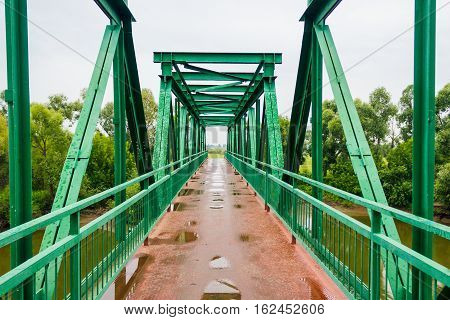 Pedestrian iron bridge over the river on a rainy day