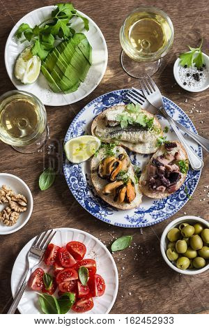 Delicious tapas - sandwiches sardines mussels octopus grape olives tomato avocado and white wine on wooden table top view. Flat lay