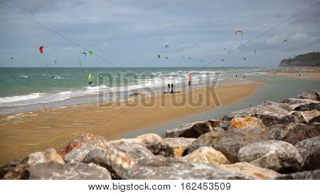 WISSANT, FRANCE - AUGUST 28, 2016: The beach with kite surfers. View with the Cap Blanc Nez in the background
