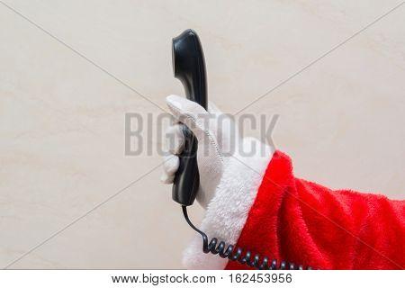 Santa Claus holding a telephone receiver horizontal