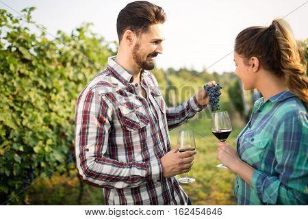 Happy young winegrowers tasting wine in vineyard