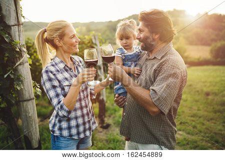 Winegrower family tasting wine in beautiful vineyard