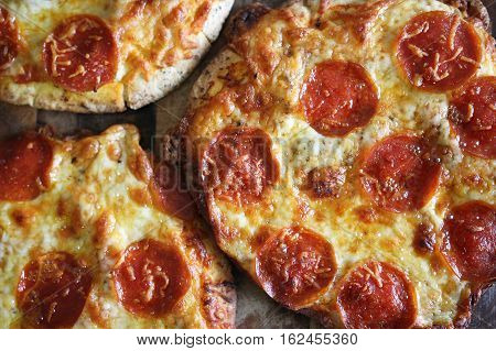 A group of small personal pan handmade fresh pepperoni pizzas are sitting on a wooden table.