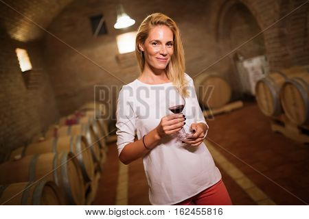 Young cute female tasting wine in winery cellar