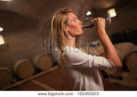 Beautiful female tasting wine in winery cellar