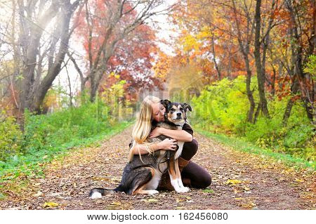 A happy and peaceful young woman is hugging her German Shepherd mix breed dog as the rest while on a walk in the woods on a fall day.