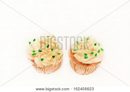 Two birthday vanilla cupcakes muffins with butter cream icing topping isolated on white background Sweet home baked cake dessert with small fir-trees sprinkles on top Christmas x-mas theme snack food
