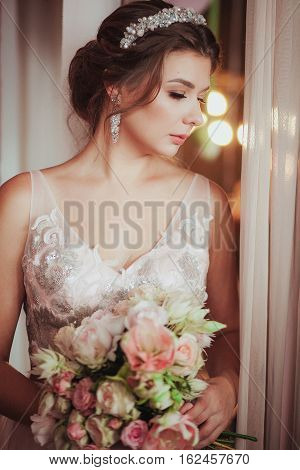 romantic Woman in pink bridal dress sitting on brown armchair. Face with closed eyes lifted up. Indoor, interior, studio.
