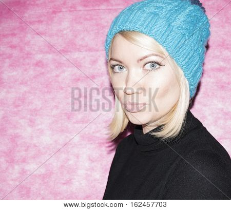 Portrait of a girl in blue knitted cap and mittens kroplin up on a pink background. Snow maiden