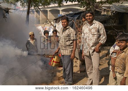 AHMADABAD, INDIA - OCTOBER 31, 2007: Men spraying insecticide powder amongst the dwellings of a shanty town Ahmadabad, Gujarat, India.